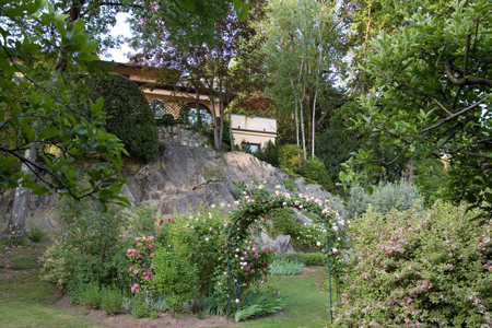 La casa vista dal giardino inferiore; arco di rose Pierre de Ronsard, sulla destra, in primo piano arbusto in fiore di Weigela